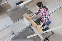 High angle view of female carpenter using a sliding table saw in workshop
