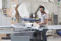 Male carpenter using a sliding table saw in workshop