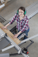 High angle portrait of happy female carpenter using a sliding table saw in workshop