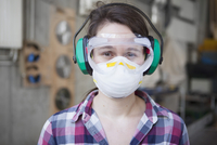 Portrait of female carpenter in protective workwear at workshop