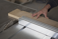 Cropped image of carpenter using sliding table saw in workshop