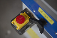 Close-up, high angle view of stop button of sliding table saw in workshop