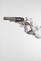 Cropped hands of bride holding handgun against white background