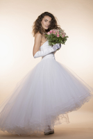 Side view portrait of young bride holding bouquet against colored background