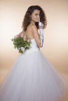 Side view portrait of bride showing silence gesture while hiding bouquet against colored background
