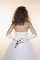 Rear view of bride holding handgun against colored background