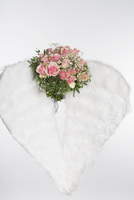 Flower bouquet and angel wings against white background