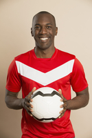 Portrait of happy soccer player holding ball against colored background