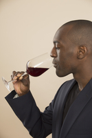 Well-dressed man tasting red wine against colored background