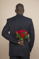 Rear view of well-dressed man holding roses against colored background