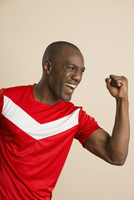 Enthusiastic soccer player with clenched fist against colored background