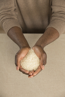 High angle view of rice in cupped hands at table