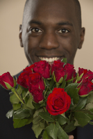Portrait of happy man with roses against colored background