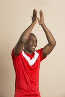 Happy soccer player applauding against colored background