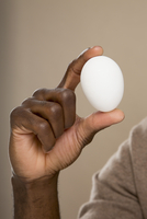 Cropped hand holding egg against colored background