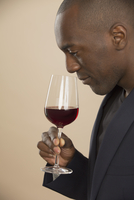 Man smelling red wine against colored background
