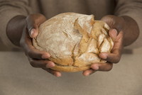 Midsection of man holding bread loaf at table