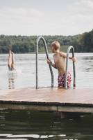Boy looking at friend sticking out legs out of lake
