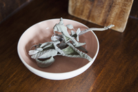 Dry leaves in bowl on table at home
