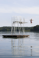 Rear view of boy jumping in lake against sky