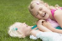 Happy girl lying on sister in backyard