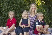 Portrait of happy family sitting at backyard