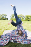 Boy practicing headstand at backyard during sunny day