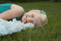 Portrait of smiling girl lying on grassy field at backyard