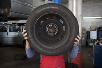 Mechanic holding tire in front of face at garage