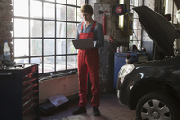 Mechanic using laptop by window at garage