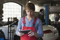 Mechanic using digital tablet at garage