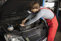 Mechanic examining car engine at workshop