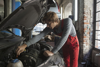 Mechanic examining car engine at auto repair shop