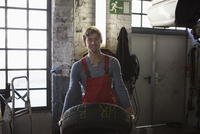 Portrait of smiling mechanic holding tire at garage