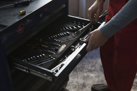 Midsection of mechanic removing tools from drawer at garage