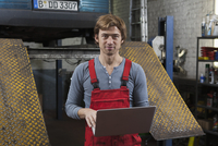 Portrait of mechanic holding laptop at garage