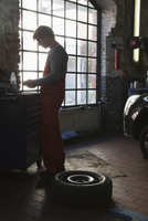 Side view of mechanic standing by window at garage