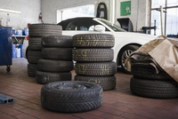 Stacked tires by car in garage