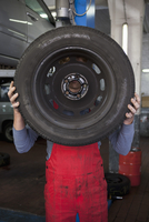 Mechanic holding tire in front of face at workshop