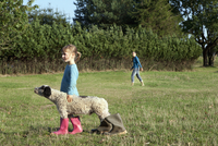 Side view of girl standing with dog wearing rubber boots on field
