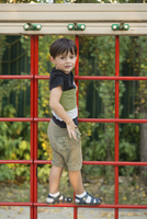 Portrait of boy standing on climbing wall at park