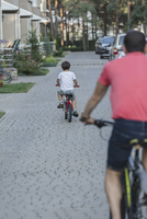 Rear view of father and son riding bicycle on street