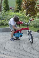 Boy adjusting bicycle seat