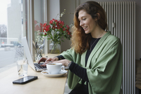 Smiling woman using laptop and having coffee at table