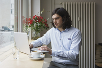 Man using laptop while having coffee at cafe