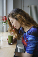 Side view of young woman drinking juice at cafe