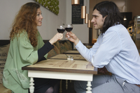 Side view of friends toasting wine while sitting at cafe