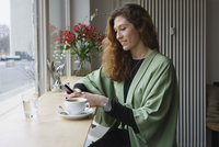 Young woman using phone and having coffee at cafe