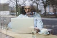 Man using laptop and having coffee seen through glass window