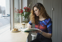 Young woman reading book while having breakfast at cafe